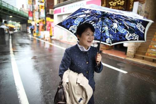 """Off to flip a table at the PM!""  Hiromi Nakasaki holding an umbrella poses for a photograph in Tokyo. Now, Nakasaki visits Tokyo every month to promote herself as a freelance business consultant. Photographer: Tomohiro Ohsumi/Bloomberg"