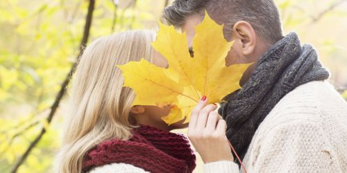 Getty. [Image: a short person with long hair and a tall person with short hair kissing behind a big yellow leaf.]